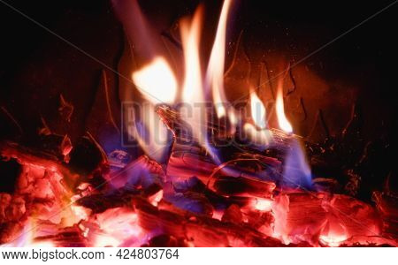 Fire In The Fireplace With Glass Close-up. Firewood Is Burning In The Fireplace