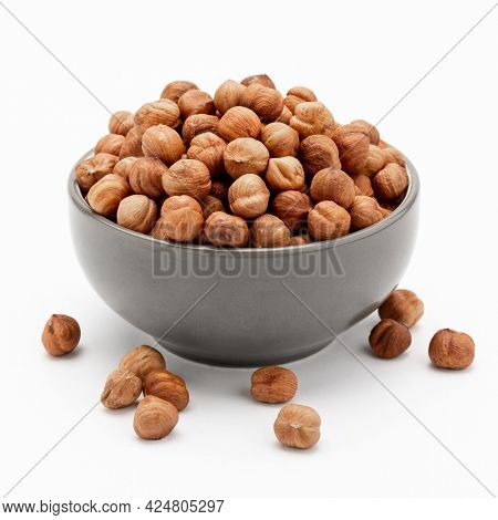 Peeled hazelnuts in a bowl and a few nuts scattered around on a white background. Template for designers.
