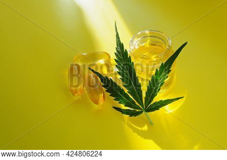 Marijuana Oil, Cbd Recreation. Fresh Cannabis Leaf And Medical Pills On Yellow Background, Top View,