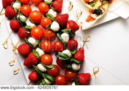 Top View Of Canapes Of Cherry Tomato, Cheese And Strawberries