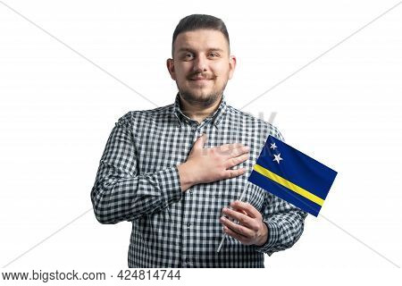White Guy Holding A Flag Of Curacao And Holds His Hand On His Heart Isolated On A White Background W