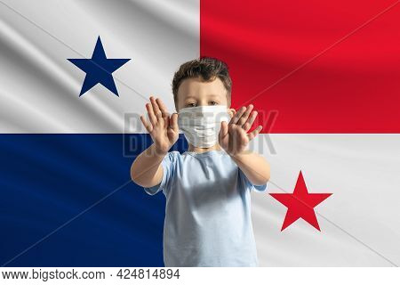 Little White Boy In A Protective Mask On The Background Of The Flag Of Panama. Makes A Stop Sign Wit