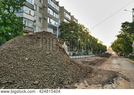 A large pile of rubble against the backdrop of a long street. Construction work in the city on the r