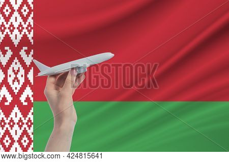 Airplane In Hand With National Flag Of Belarus. Travel To Belarus.