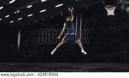 One Young Sportsman Basketball Player Training In Gym, Idoors Isolated On Dark Background. Concept O