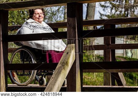 Woman In Wheelchair On Bridge At Sunny Day. Mid-age Women With Wheelchair Enjoying First Sun At Spri