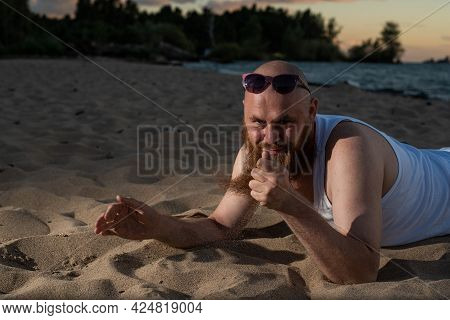 A Humorous Portrait Of A Brutal Man In A T-shirt And Boxers On The Beach At Sunset