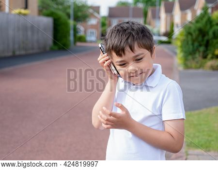 Portrait Happy Schoolboy Talking On Mobile Phone With Friend. Cute Child Using Smart Phone While Sta