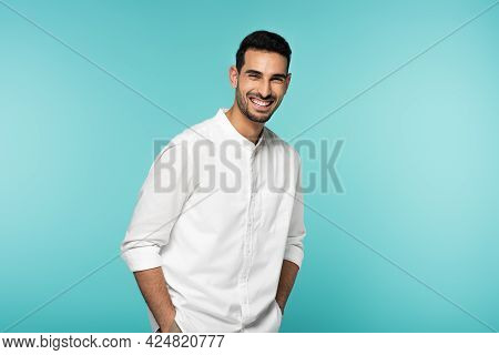 Happy Muslim Man In White Shirt Looking At Camera Isolated On Blue