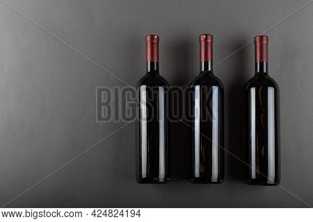 A Corked Three Bottle Of Red Wine On A Gray Office. Alcoholic Drink. Winemaking Concept. Space For T