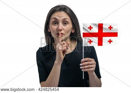 Happy Young White Woman Holding Flag Of Georgia And Holds A Finger To Her Lips Isolated On A White B