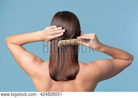 Woman combing her sleek hair
