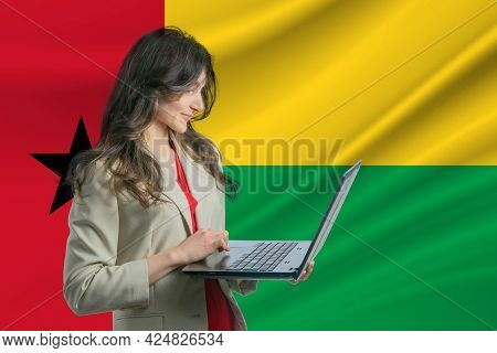 Freelance In Guinea-bissau. Beautiful Young Woman Freelancer Uses Laptop Computer Against The Backgr