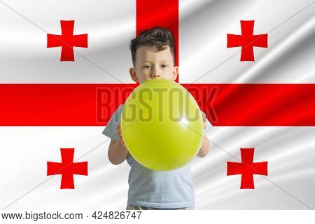 Children's Day In Georgia. White Boy With A Balloon On The Background Of The Flag Of Georgia. Childr