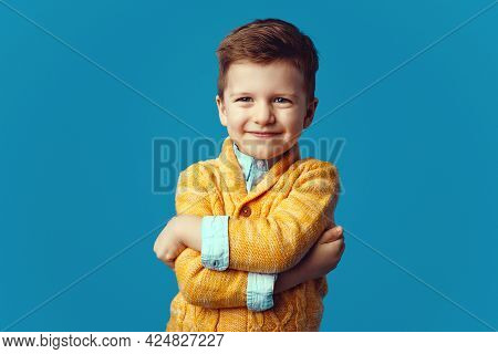 Young Boy In Yellow Cardigan Smiling And Posing With Hands Crossed On Blue