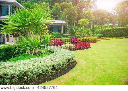 Front Yard. Landscape Design With Multicolored Shrubs Intersecting With Bright Green Lawns Behind Th