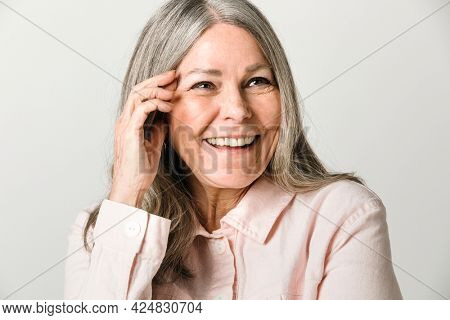 Closeup of cheerful senior woman in a studio shoot