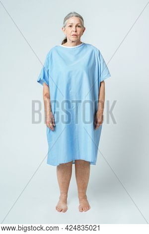 Sad senior patient in a hospital gown