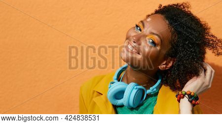 Portrait Of A Laughing Woman With Vitiligo Wearing In Blue Headphones And Colorful Clothes On Backgr