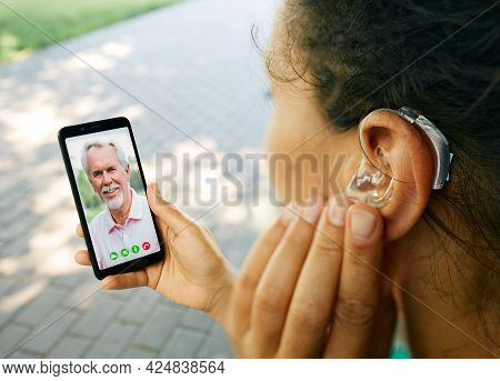 Adult Woman With A Hearing Aid In Her Ear Communicates With Her Father Via Video Communication Via A