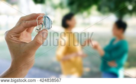 Hearing Solutions. Last Generation Of Hearing Aid Device In Human Hand With Unfocused Talking People