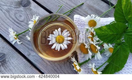 Chamomile Tea Close-up On A Wooden Background. Summer Still Life With Wildflowers And Chamomile Drin