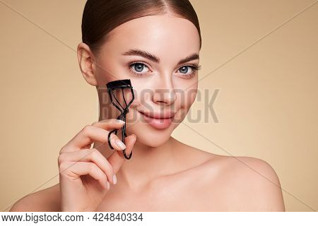 Close Up Of A Beautiful Young Woman Curling Her Eyelashes. Eyelash Extensions