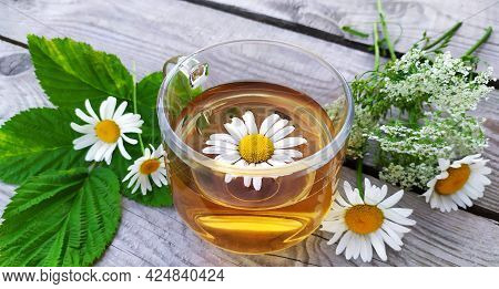 Chamomile Tea In A Glass Cup Close-up On A Wooden Background. Floral Background. Summer Still Life W