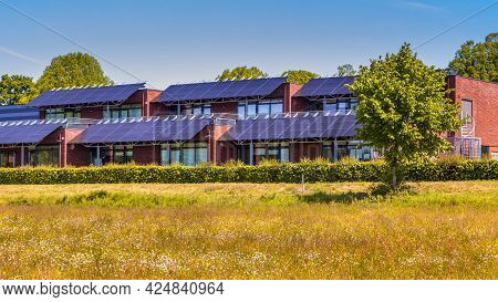 Public School Building With Solar Panels Utilized As Sunlight Protection. Shading The Classrooms Whi