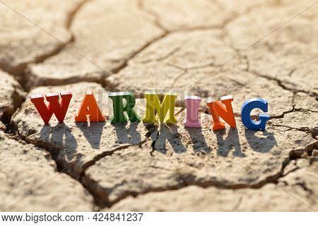 Text Warming on arid cracked soil. Concept of climate change.