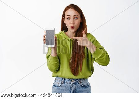 Surprised Redhead Woman Pointing Finger At Smartphone App, Gasping In Awe, Showing Interesting Appli