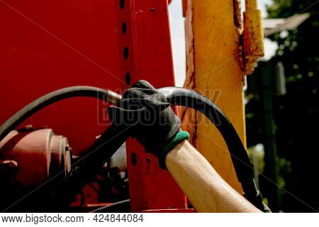 A Woman's Hand In A Rubber Glove Holds A Watering Hose. The Hose Must Be Secured To The Sprinkler.