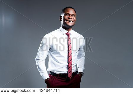 Happy African American Businessman With Hands In Pockets Smiling And Looking At Camera