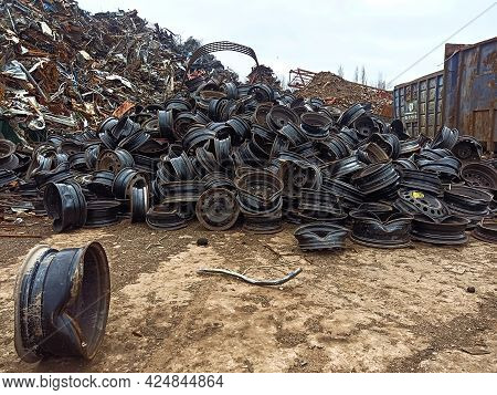 A Pile Of Broken Car Rims In A Junkyard. Worn Metal Car Rims Ready For Transportation For Recycling