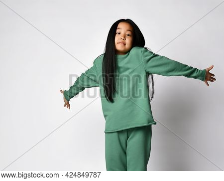 Cute Emotional Asian Preteen Girl In Green Clothing Being At Loss Showing Dont Know Helpless Gesture