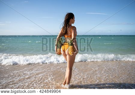 Sporty Back With Sexy Butt Of A Beautiful Woman In Bikini With A Pineapple On Sea Background With Co