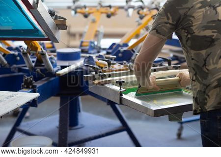 Worker And Serigraphy Silk Screen Print Process At Clothes Factory.