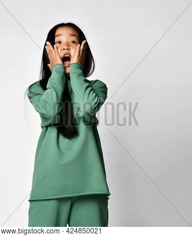 Shocked Surprised Asian Preteen Girl In Green Clothing Touching Cheeks With Both Hands Standing Agai