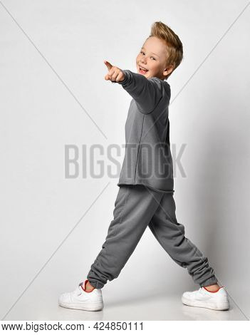 Teenager Boy With A Happy Smile, Turning And Pointing His Finger At The Camera, Studio Shot On A Whi
