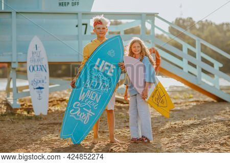Cute Teen Boy And Young Pretty Girl In Summer Clothes Posing With Surfboards Against Blue Lifeguard