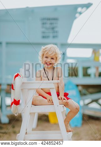 Young Pretty Curly Boy Sitting On High White Chair With Lifeline And Posing With Whistle On The Beac