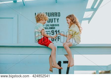 Blond Curly Young Boy And Girl In Summer Clothes Sitting Up Blue Lifeguard Tower And Playing. Summer