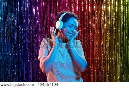 nightlife, technology and people concept - happy young african american woman in headphones listening to music and dancing at party in neon lights over rainbow foil curtain background