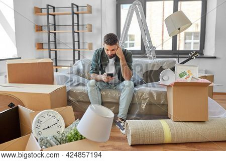 moving, eviction and real estate concept - sad man with smartphone and boxes at new home