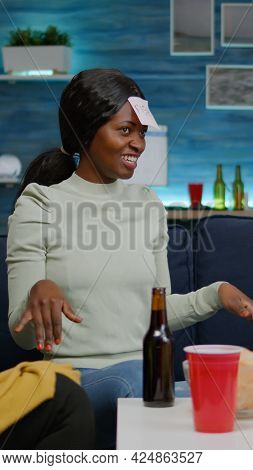 Afro American Woman Having Attaching Sticky Notes On Forehead Playing Guess Who Game With Friends Du