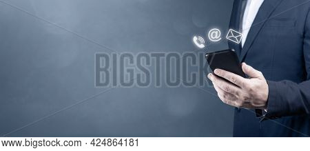 Contact Us. Businessman Holding Cell Phone With With Mail, Phone, Email Icon. Cutomer Support Concep
