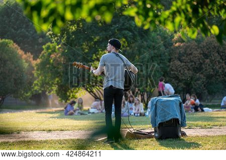Street Musician Plays The Guitar In The Park. Summer Green Park, Rock Musician Gives A Free Concert