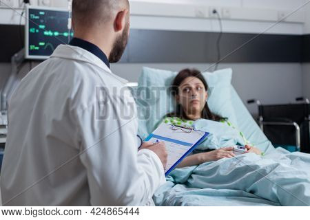 Oncologist Practitioner Doctor Explaining Sickness Diagnose Writing Medical Disease Treatment On Cli