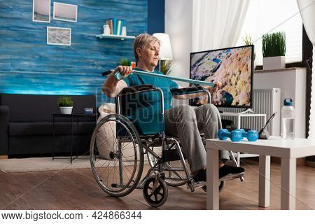 Invalid Senior Woman In Wheelchair Holding Resistance Elastic Band Stretching Body Muscle Recovering