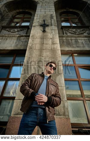 Men's fashion. Stylish young man in sunglasses and leather jacket stands on a city street and looks at his wristwatch. Lifestyle.